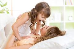 Ευτυχές παιχνίδι mom με το παιδί της στην απόλαυση κρεβατιών Στοκ φωτογραφία με δικαίωμα ελεύθερης χρήσης