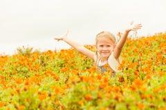 Ευτυχές παιδάκι με αυξημένος επάνω στα όπλα στον πράσινο τομέα των λουλουδιών στοκ εικόνα