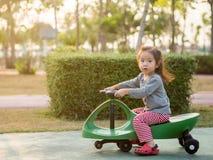 Ευτυχές παιδί, ασιατικό παιδί μωρών που παίζει ένα αυτοκίνητο ταλάντευσης Στοκ φωτογραφία με δικαίωμα ελεύθερης χρήσης