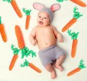 Ευτυχές παιδί μωρών στο κοστούμι ένα λαγουδάκι κουνελιών με το καρότο σε ένα μόριο Στοκ φωτογραφία με δικαίωμα ελεύθερης χρήσης