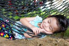 Ευτυχές παιδί που απολαμβάνει και που χαλαρώνει στην αιώρα, γλυκό όνειρο και sm Στοκ Εικόνες