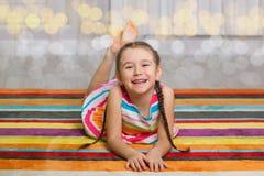 Ευτυχές παιδί που βρίσκεται στο υπόβαθρο ταπήτων χρώματος Στοκ εικόνα με δικαίωμα ελεύθερης χρήσης