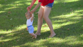 Ευτυχές παιδί που κάνει τα πρώτα βήματα σε ένα πάρκο απόθεμα βίντεο