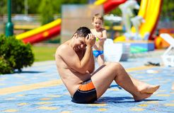 Ευτυχές παιδί που καταβρέχει το νερό στον πατέρα στο aquapark Στοκ Εικόνα