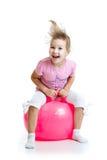 Ευτυχές παιδί που πηδά στην αναπηδώντας σφαίρα που απομονώνεται Στοκ Φωτογραφία