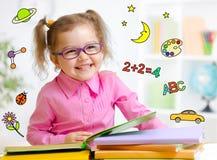Ευτυχές παιδί στα γυαλιά που διαβάζει το βιβλίο νωρίς στοκ εικόνες