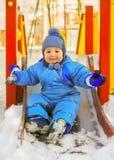 Ευτυχές παιδί στην παιδική χαρά παιδιών το χειμώνα Στοκ φωτογραφία με δικαίωμα ελεύθερης χρήσης