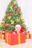 Ευτυχές παιδί στο καπέλο Χριστουγέννων στο κιβώτιο δώρων Στοκ εικόνα με δικαίωμα ελεύθερης χρήσης