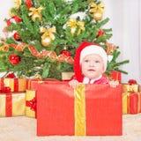 Ευτυχές παιδί στο καπέλο Χριστουγέννων στο κιβώτιο δώρων Στοκ Εικόνα