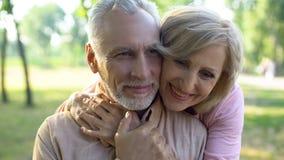 Ευτυχές παλαιό αγκάλιασμα ζευγών, που στηρίζεται στο πάρκο μαζί, στενότητα παππούδων και γιαγιάδων στοκ φωτογραφίες