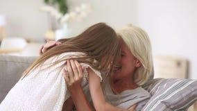 Ευτυχές παλαιό παιχνίδι αγκαλιάς εγγονών γιαγιάδων και παιδιών στον καναπέ φιλμ μικρού μήκους