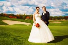 Ευτυχές παντρεμένο ζευγάρι στον τομέα γκολφ Στοκ Φωτογραφία