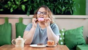 Ευτυχές παχουλό doughnut δαγκώματος γυναικών με το ζωηρόχρωμο παγώνοντας επιδόρπιο απόλαυσης στο μέσο πυροβολισμό καφέδων απόθεμα βίντεο