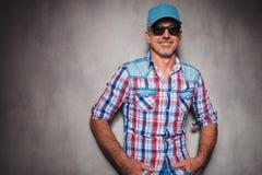 Ευτυχές περιστασιακό άτομο ενδυμάτων και trucker τζιν στο χαμόγελο καπέλων Στοκ Εικόνα