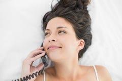 Ευτυχές περιστασιακό brunette στις άσπρες πυτζάμες που καλούν με ένα τηλέφωνο Στοκ φωτογραφία με δικαίωμα ελεύθερης χρήσης