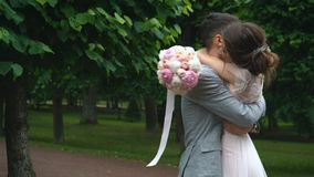 Ευτυχές περπάτημα αγκαλιάσματος newlyweds στον πράσινο κήπο απόθεμα βίντεο