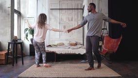 Ευτυχές πολυφυλετικό ζεύγος στις πυτζάμες που κρατά τα χέρια και το χορό Η γυναίκα και ο άνδρας στην εύθυμη διάθεση έχουν τη διασ απόθεμα βίντεο