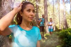 Ευτυχές πορτρέτο γυναικών με την πορεία ιχνών πεζοπορίας ανδρών και κοριτσιών στα δασικά ξύλα κατά τη διάρκεια της ηλιόλουστης ημ Στοκ Εικόνα
