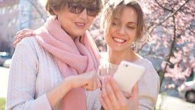 Ευτυχές πορτρέτο μιας ώριμης γυναίκας και του νέου φίλου της με ένα smartphone Θηλυκή φιλία, θηλυκή επιχείρηση, δίκτυο απόθεμα βίντεο
