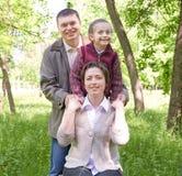 Ευτυχές πορτρέτο οικογενειών και παιδιών Πάρκο πόλεων σε θερινή περίοδο Όμορφο τοπίο με τα δέντρα και την πράσινη χλόη Στοκ Εικόνες