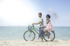 Ευτυχές ποδήλατο γύρου μικρών κοριτσιών και αγοριών Στοκ Εικόνα