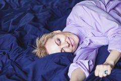 ευτυχές πρωί Η όμορφη γυναίκα βρίσκεται στο μπλε φύλλο Στοκ φωτογραφία με δικαίωμα ελεύθερης χρήσης