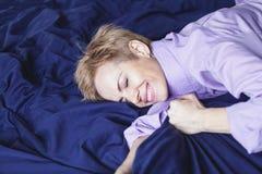 ευτυχές πρωί Η όμορφη γυναίκα βρίσκεται στο μπλε φύλλο Στοκ Φωτογραφία