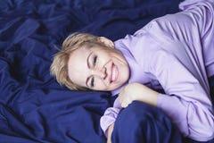 ευτυχές πρωί Η όμορφη γυναίκα βρίσκεται στο μπλε φύλλο Στοκ Εικόνες