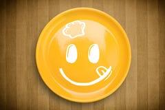 Ευτυχές πρόσωπο κινούμενων σχεδίων smiley στο ζωηρόχρωμο πιάτο πιάτων Στοκ Εικόνα