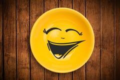 Ευτυχές πρόσωπο κινούμενων σχεδίων smiley στο ζωηρόχρωμο πιάτο πιάτων Στοκ Φωτογραφία