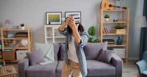Ευτυχές πρόσωπο που έχει τη διασκέδαση με τα αυξημένα γυαλιά πραγματικότητας που φορούν την κάσκα στο σπίτι απόθεμα βίντεο