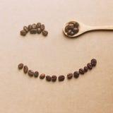 Ευτυχές πρόσωπο που διαμορφώνεται των φασολιών καφέ με το ξύλινο κουτάλι στοκ φωτογραφίες με δικαίωμα ελεύθερης χρήσης