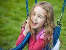 Ευτυχές πρόσωπο σε ένα μικρό κορίτσι που παίζει με την ταλάντευση Στοκ Εικόνα
