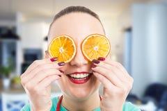 Ευτυχές πρόσωπο χαμόγελου μιας γυναίκας που καλύπτει τα μάτια της με πορτοκαλή slic στοκ φωτογραφία με δικαίωμα ελεύθερης χρήσης