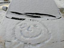 Ευτυχές πρόσωπο χιονιού στο παράθυρο αυτοκινήτων Χαμόγελο στο χιόνι, ευτυχής εύθυμη εικόνα στοκ φωτογραφία με δικαίωμα ελεύθερης χρήσης