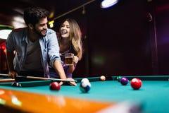 Ευτυχές σνούκερ παιχνιδιού νεαρών άνδρων με τη φίλη του Ευτυχές αγαπώντας ζεύγος στοκ εικόνες