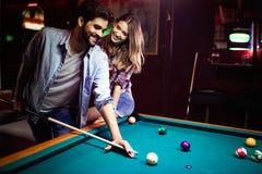 Ευτυχές σνούκερ παιχνιδιού νεαρών άνδρων με τη φίλη του Ευτυχές αγαπώντας ζεύγος στοκ φωτογραφία