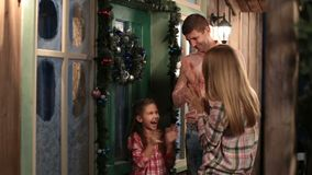 Ευτυχές στεφάνι οικογενειακών κρεμώντας Χριστουγέννων στην πόρτα απόθεμα βίντεο