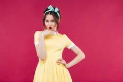 Ευτυχές στοχαστικό κορίτσι pinup στο κίτρινο φόρεμα που στέκεται και που θέτει Στοκ Εικόνα