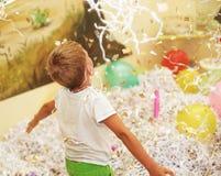 Ευτυχές συγκινημένο γελώντας παιδί κάτω από το λαμπιρίζοντας ντους κομφετί Στοκ Φωτογραφία