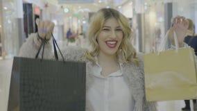 Ευτυχές συγκινημένο εφηβικό ξανθό κορίτσι που χαμογελά και που παρουσιάζει τσάντες αγορών της στη κάμερα στη λεωφόρο - απόθεμα βίντεο