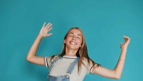 Ευτυχές συγκινημένο κορίτσι με μακρυμάλλες να πηδήξει έξω με τα χέρια που αυξάνονται Όμορφα άλματα και γέλιο κοριτσιών στην ευτυχ απόθεμα βίντεο