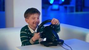 Ευτυχές συγκινημένο videogame παιχνιδιού μικρών παιδιών με τον αγώνα της ρόδας απόθεμα βίντεο
