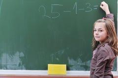 Ευτυχές σχολικό κορίτσι στις κλάσεις math στοκ εικόνα