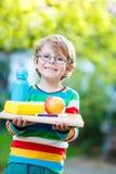 Ευτυχές σχολικό αγόρι με τα βιβλία, το μπουκάλι μήλων και ποτών Στοκ Εικόνες
