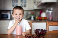 Ευτυχές σχολικό αγόρι που πίνει έναν υγιή καταφερτζή ως πρόχειρο φαγητό Στοκ Εικόνα