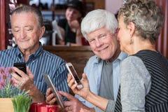 Ευτυχές τρίο στο σπίτι καφέ που χρησιμοποιεί τις ηλεκτρονικές συσκευές Στοκ Εικόνες