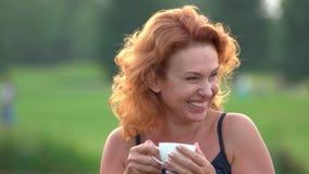 Ευτυχές τσάι κατανάλωσης γυναικών χαμόγελου υπαίθρια απόθεμα βίντεο