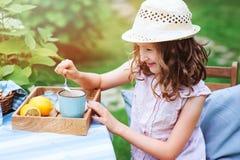 Ευτυχές τσάι κατανάλωσης κοριτσιών παιδιών με τα λεμόνια στο θερινό κήπο Στοκ εικόνες με δικαίωμα ελεύθερης χρήσης