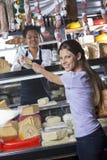 Ευτυχές τυρί αγοράς γυναικών από τον εργαζόμενο στο κατάστημα Στοκ Εικόνες